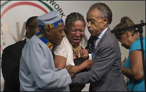 Esaw Garner, wife of Eric Garner, breaks down in the arms of Rev. Herbert Daughtry, center, and Rev. Al Sharpton, right, during a rally Saturday for Eric Garner at the National Action Network headquarters.