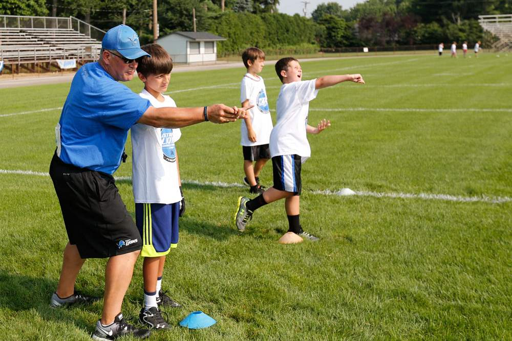 SPT-lionscamp22pCamp-director-and-coach-Jim-Hamilton-works-with-Kaden-H-on-passing-the-football