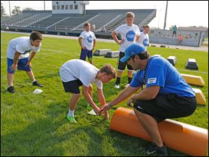 Coach Pat Sharrow, right, and  Matthew Z. demonstrate the correct stance for an offensive lineman.