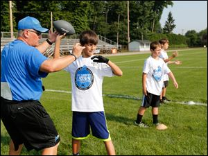 Camp director and coach Jim Hamilton works with Kaden H. on passing the football.
