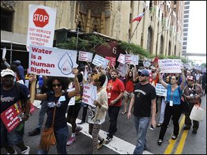 Protesters march over the controversial water shut-offs Friday, July 18, 2014, in Detroit, Mich.