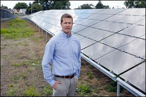Jason Slatter, director of solar for Rudolph Libbe, stands in front of the companye's solar array project, one of the largest of its kind in this area, off of Spencer Road.