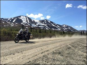 Chris Day churns up dust on the Denali Highway of Alaska during an 865-mile ride around Alaska with seven of his friends.