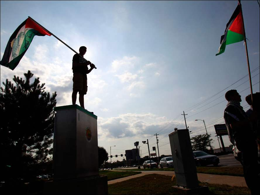 Adam Abuhummos, left, waves the Palestinian flag atop an electrical box.