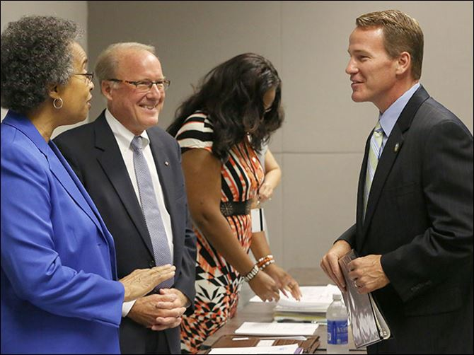 b4husted Lucas County Board of Election members Brenda Hill, left, and Peter Handwork, center, greet Secretary of State Jon Husted right, before opening a special meeting on Tuesday.