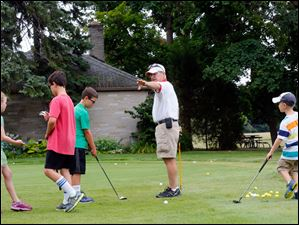 Golf coach Kip Hartzell teaches campers how to putt.