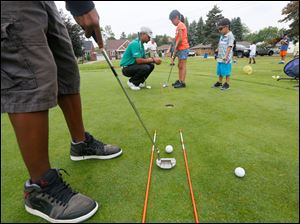 Golf pro Milton Carswell Jr., left, helps Anessa Santellana, 9, a proper putt. Her little brother Michael Rosales, 4, far right, watches.