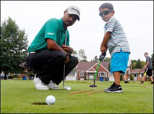 Golf pro Milton Carswell Jr., left, helps Michael Rosales, 4, a proper putt.