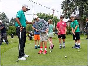 Golf pro Milton Carswell Jr., left, speaks with Palmer Yenrick, right, 13, who is a member of the Toledo Junior Golf Association.