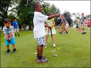 Isaac Romero, 5, from Toledo, marvels at a ball he hit while practicing chipping with other campers.