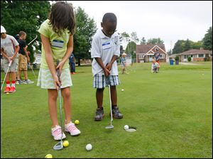 Isabella Romero, left, 6, and Isaac Romero, 5, right, practice putting the ball.