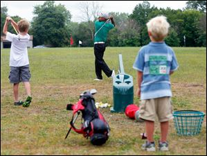 Milton Carswell Jr. center, shows brothers Brock Fussell, left, 8, and Dane Fussell, 5, right, how to swing the club.