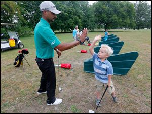 Pro Milton Carswell Jr., left, gives Dane Fussell, 5, right, from Toledo, a hi-five for a great golf swing.