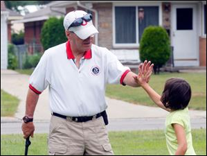 Golf coach Kip Hartzell, left, gives Isabella Romero, right, 6, a hi-five after she putt the ball.