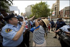 Police try to stop a woman wielding a cane from hitting another woman, not pictured, who was supporting Israel in its war with Hamas members in the Gaza Strip, during a rally at John F. Kennedy Plaza, also known as Love Park, in Philadelphia on Wednesday.