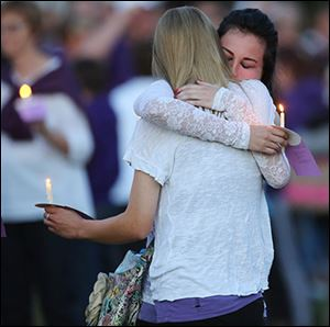 Bowling Green State University students Ellen Frankart, left, and Rebecca Winebrenner hug during a vigil for their friend.