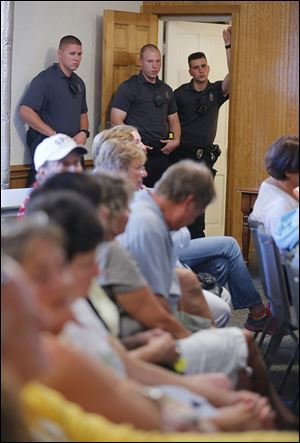 Put-in-Bay police officers listen during the meeting.
