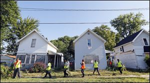 Members of Pathway mow and clean debris from homes on Earl Street near Kingston Avenue.