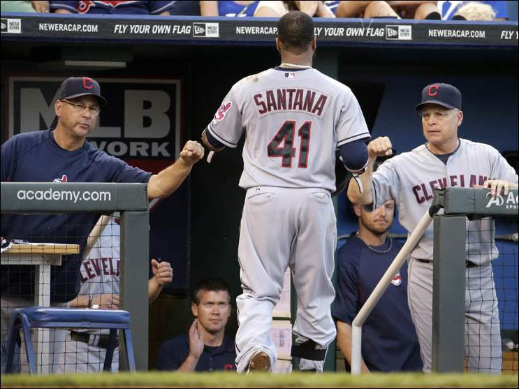 Cleveland Indians' Carlos Santana celebrates as he enters the dugout after hitting a solo home run.