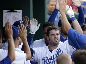 Kansas City Royals' Mike Moustakas celebrates in the dugout after hitting a solo home run.