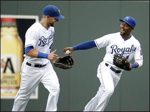 Kansas City Royals center fielder Jarrod Dyson (1) and left fielder Alex Gordon, left, celebrate after Dyson caught a fly ball hit by Cleveland Indians' Michael Brantley.