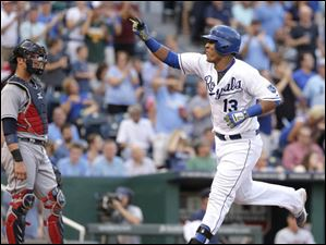 Kansas City Royals' Salvador Perez (13) crosses the plate past Cleveland Indians catcher Yan Gomes after hitting a solo home run.