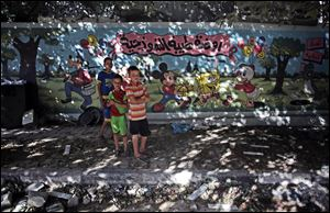"Palestinian boys stand next to wall with murals and Arabic writing that reads ""Tiba standard nursery,"" next to a destroyed house following an overnight Israeli strike Friday in Gaza City."