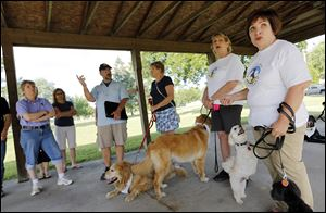 Tina Yoppolo, right, president of Toledo Unleashed, and Sue Joseph, left, treasurer of the group, speak to neighborhood residents about the city's dog park.