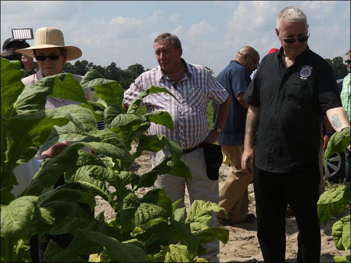 FLOC President Baldemar Velasquez, not pictured, discusses the working condition differences between documented and undocumented migrants as U.S Rep. Marcy Kaptur (D-OH), left, British Members of Parliament James Sheridan, center, and Ian Lavery, right, inspect tobacco plants.