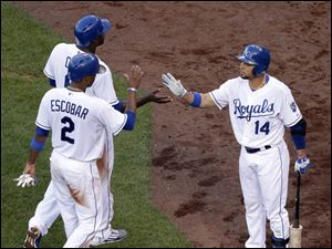 Kansas City Royals' Alcides Escobar (2) and Lorenzo Cain (6) celebrate with Omar Infante (14) after scoring on a triple by Norichika Aoki.