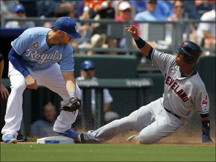 Cleveland Indians' Jose Ramirez, right, is safe at third as Kansas City Royals third baseman Mike Moustakas, left, is late with the tag.