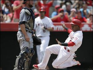 Los Angeles Angels' Erick Aybar, right, slides into home plate to score on a throwing error by Detroit Tigers pitcher Rick Porcello as Tigers catcher Bryan Holaday, left, looks on.