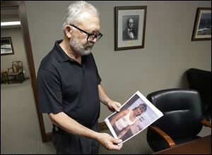 "Salt Lake City attorney Jesse Trentadue holds a photograph of his brother taken in the early 80's showing his dragon tattoo on his left forearm, which fit the description the FBI was circulating of  ""John Doe"