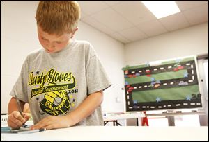 Fourth-grader Collin Berryman, 9, writes his name on a slip of paper to enter into a drawing for a grand prize during the summer math club at Coy.