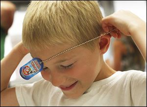 '‍Math wizard' William Hanthorn, 6, puts his dog tag on after earning the title for his work in the summer math club.