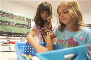 Maci Karrick, 10, left, and Natalie Karrick, 7, pick out prizes during the summer math club at Coy Elementary School in Oregon. The two girls selected from prizes Tuesday that included candy, bracelets, and dog tags, purchased with money donated by Coy'‍s parents association.