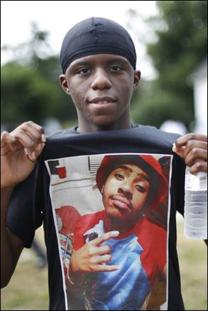Cyrus Nimene, 18, holds out his T-shirt with an image of his friend Tyler McIntoush, 16, on it during the annual anti-gang violence  march in Toledo.