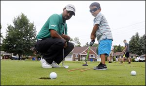 PGA pro Milton Carswell, Jr., helps Michael Rosales, 4, sink a putt during the '‍Mornings with Milton' children's summer golf camp at Collins Park Golf Course in East Toledo.