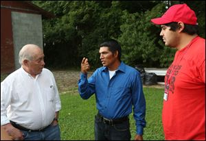 FLOC President Baldemar Velasquez, left, speaks with a migrant worker, who agreed to be photographed but declined to be named, center, outside the cinder block building where he lives.