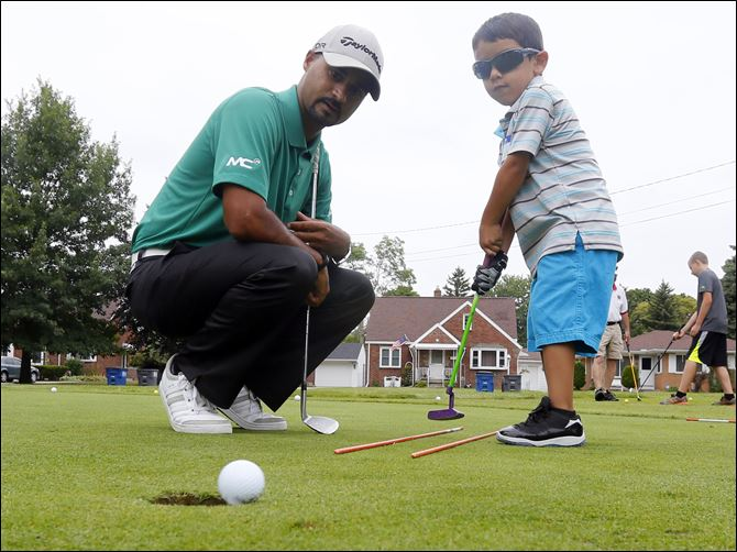 CTY GOLF241 PGA pro Milton Carswell, Jr., helps Michael Rosales, 4, sink a putt during the '‍Mornings with Milton' children's summer golf camp at Collins Park Golf Course in East Toledo.