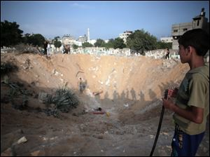 Palestinian check a crater caused by an Israeli strike at a cemetery in the Jabaliya refugee camp, northern Gaza Strip, today.