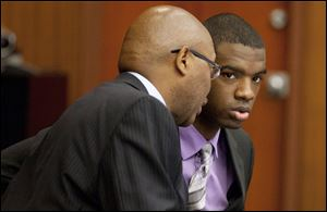 Assistant Washtenaw County Public Defender Lorne Brown, left, talks to his client, Ed Thomas during Thomas' trial.