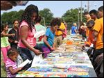 Cynthia Carter, center left, smiles as her daughter Malayiah, 2, picks out a book during a cookout and book giveaway put on Tuesday by the organization Books 4 Buddies and Toledo Public Schools near the LMHAS's Weiler Homes in East Toledo.