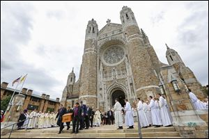 Pallbearers carry the casket of Auxiliary Bishop Robert Donnelly from Our Lady, Queen of the Most Holy Rosary Cathedral as clergy members  sing after his funeral.