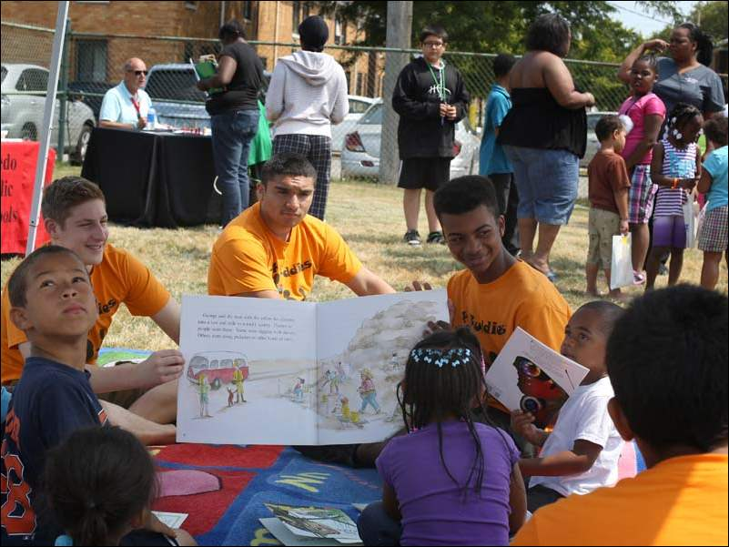 Books 4 Buddies ambassadors Zane Kruszynski, 16, left, Rudy Basquez, 17, center, and Jason Johnson, 14, right, read aloud to children during a cook out and book giveaway.