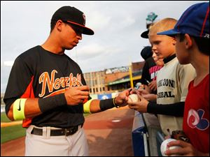 Norfolk Tides left fielder Quintin Berry, left, hands a baseball back to Jayden Seiler, right, 9, after autographing it.  Berry is a former Mud Hen.