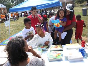 Johnathan, 8, left, and Kamyah, 7, center left, grab free books as their parents Edgar and Kiki Santamaria sign up their sister for Head Start