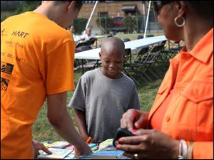 Tayveon McCory, 11, center, smiles as he picks out a book during a cook out and book giveaway put on by Books 4 Buddies and Toledo Public Schools Tuesday.
