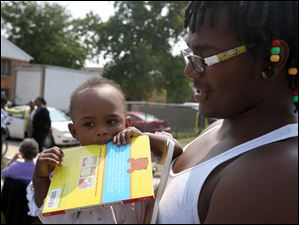 Max Gamble holds his 10-month-old daughter London during a cook out and book giveaway in East Toledo.