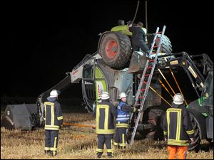 Firefighters try to set up a mechanical digger on a field near Isselburg, western Germany Tuesday. German authorities say a man was killed and several others were injured when the digger tipped over and hit them during a so-called Cod Water Challenge, a dare that has been spreading on Facebook.